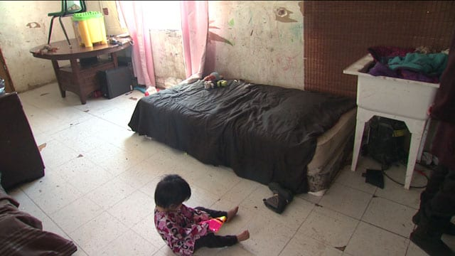 A child plays on the floor of a room in Garden Hill.