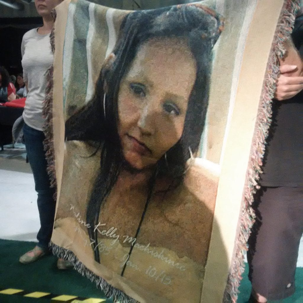 A tapestry image of Nadine Machiskinic is held up during the AFN annual general assembly in Regina.