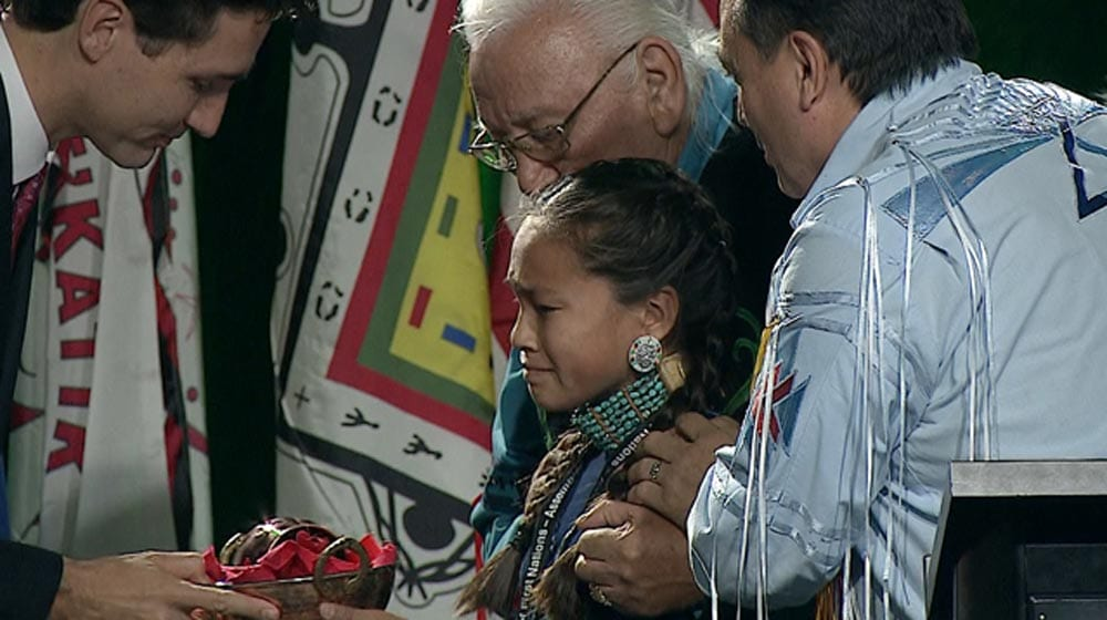 Autumn Peltier, flanked by AFN National Chief Perry Bellegarde and AFN Elder Elmer Courchene presents a water bundle to Prime Minister Justin Trudeau in December 2016.