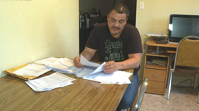 Clayton Boucher, 45, looks over court documents related to wrongful conviction recently in his North Battleford, Sask. home.
