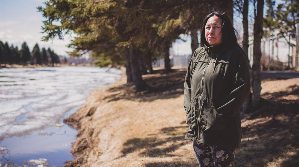 Cheryl Suggashie stands at the McIntyre River where her brother Clayton Mawakeesic was found dead in 2015.