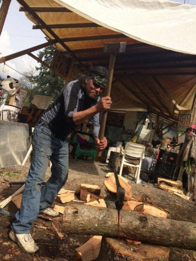 Johnny Lee, from Edmonton, chops wood at Camp Cloud near Kinder Morgan's construction site in Burnaby, B.C. on April 18, 2018. Lucy Scholey/APTN
