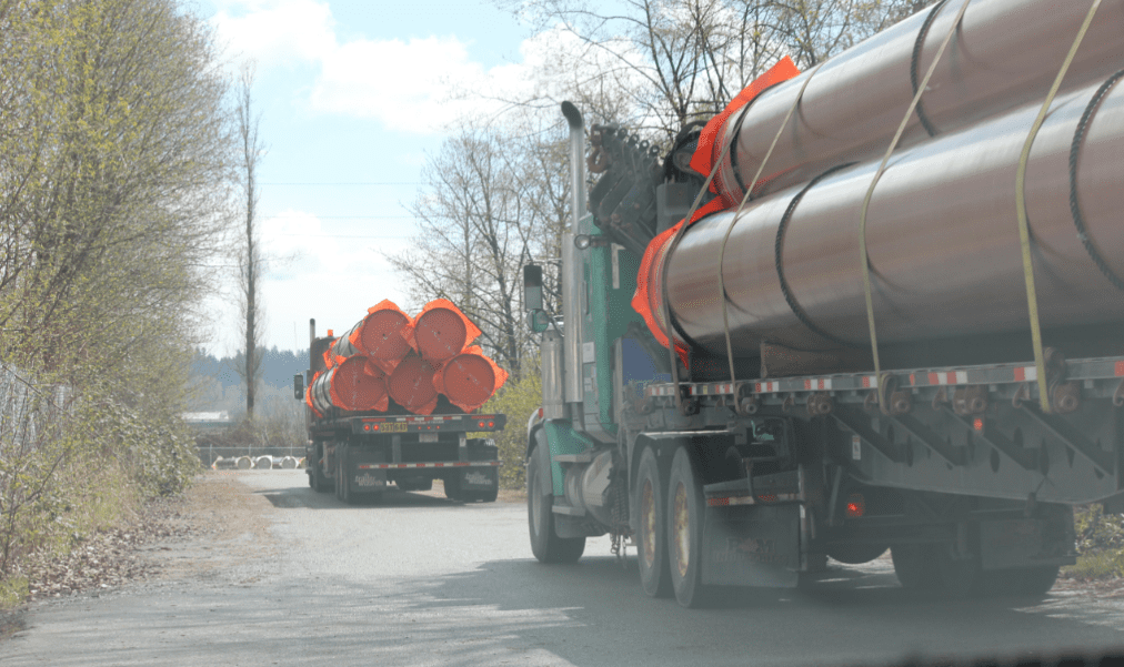 (Trucks are pictured carrying pipes travel into Kinder Morgan's New Westminster site. Contributed/Peter McCartney)
