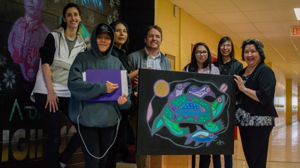 The DFC art club presents Louise Thomas with a spray painted version of her late husband's art. Photo: Willow Fiddler/APTN