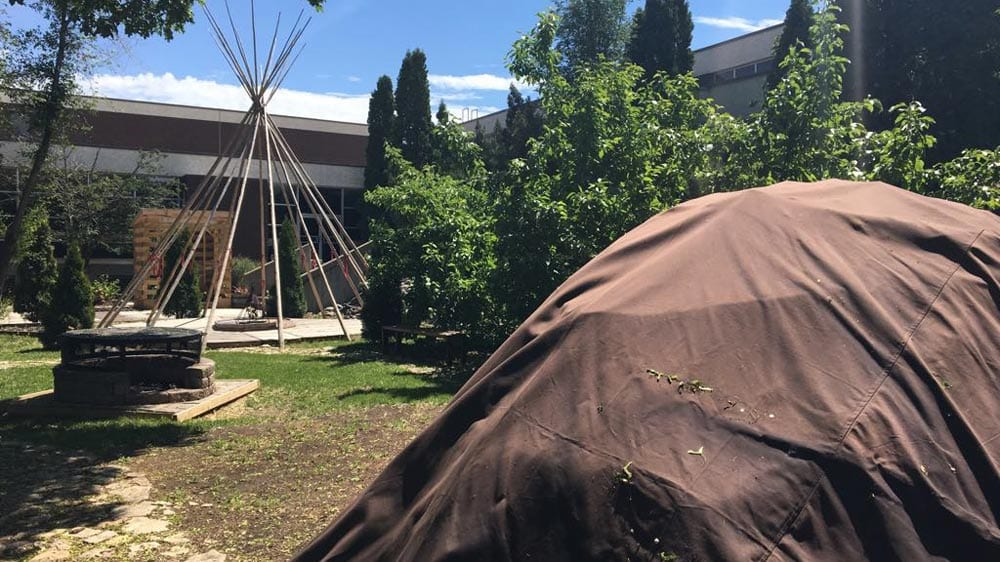A sweat lodge sits in the foreground of the RB Russell school. Students smudge every morning. Photo: Brittany Hobson/APTN