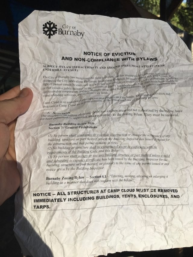 "<em style=""font-size: 16px;"">A copy of the July 18 eviction notice given to Camp Cloud water protectors by the City of Burnaby. Photo: Justin Brake/APTN)</em>"