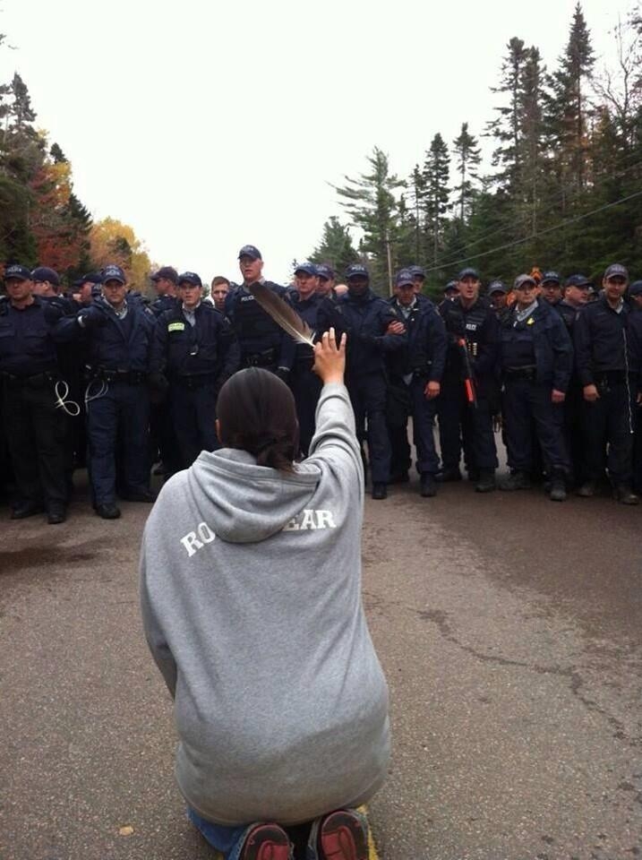 Amanda Polchies holds an eagle feather and kneels before a wall of RCMP officers on Oct. 17. APTN/Ossie Michelin