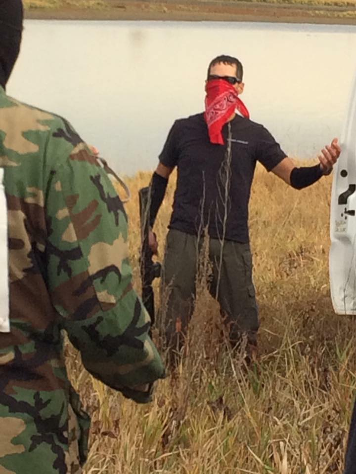 Kyle Thompson, with red kerchief over his face, holding an assault rifle during confrontation with water protectors on Oct. 27. Facebook photo