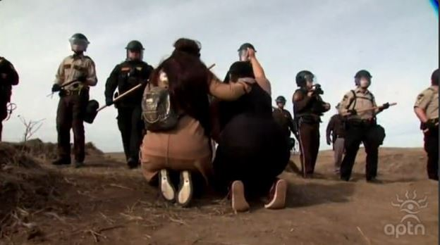 Women kneel before police line in North Dakota during law enforcement operation on Oct. 27. APTN/Photo
